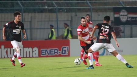 Aleksandar Rakic berusaha melewati Muhammad Tahir pada laga Madura United vs Persipura Jayapura di Liga 1 2019, Minggu (03/11/19). - INDOSPORT