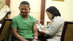 Indosport - Ekspresi lucu pemain Timnas Indonesia U-23, Gian Zola yang menahan sakit saat disuntik vaksin jelang SEA Games 2019.