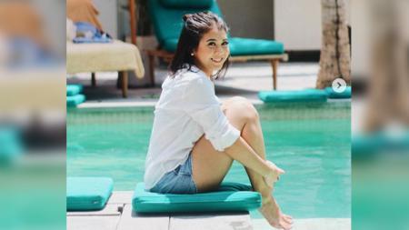 Kesha Ratuliu duduk di pinggir kolam renang. - INDOSPORT