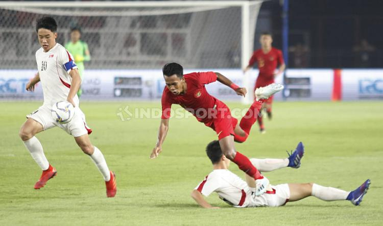 Pemain Timnas Indonesia U-19 Muhammad Supriadi berusaha menghindar dari pemain Korea Utara U-19 pada Kualifikasi Piala Asia U-19 di GBK Jakarta, Minggu (10/11/19). Copyright: Herry Ibrahim/INDOSPORT