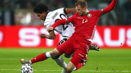 Serge Gnabry tengah terlibat perebutan bola dengan pemain Belarusia. - INDOSPORT