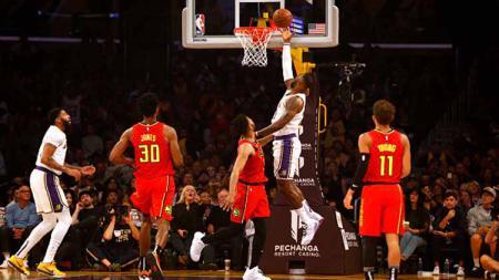 Aksi memukau bintang basket NBA dari tim LA Lakers, LeBron James saat memasukkan bola ke dalam ring dalam laga melawan Atlanta Hawks - INDOSPORT