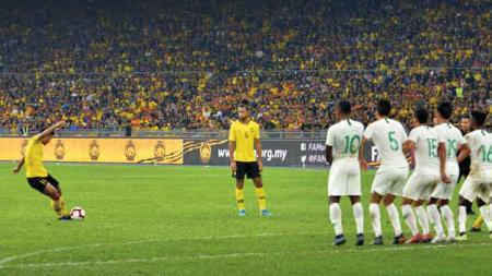 Salah satu pemain Malaysia melakukan tendangan bebas - INDOSPORT