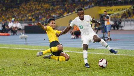 Greg Nwokolo berusaha mengontrol bola dari serangan pemain Malaysia.