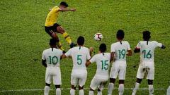 Indosport - Striker Malaysia, Muhammad Safawi Rasid, melakukan tendangan bebas ke gawang timnas Indonesia