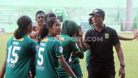 Pelatih Persebaya Putri Ridwan Anwar (bertopi) memberikan selamat ke anak didiknya usai mencetak gol ke gawang Bali United putri, Rabu (20/11/19). - INDOSPORT