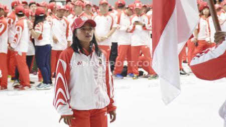 Atlet lari Triyaningsih melakukan orosesi mencium bendera Merah Putih oleh atlet pada acara pelepasan Kontingen SEA Games Indonesia 2019 di Hall A Basket GBK, Senayan, Rabu (27/11/19). - INDOSPORT