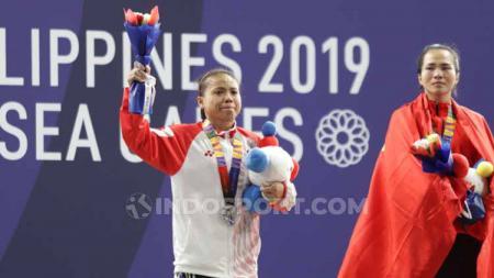 Potret kekecewaan lifter putri Indonesia, Lisa Setiawati usai gagal meraih emas di nomor 45 kg SEA Games 2019 di Nino Aquino Stadium, Minggu (01/12/19). Foto: Ronald Seger Prabowo - INDOSPORT