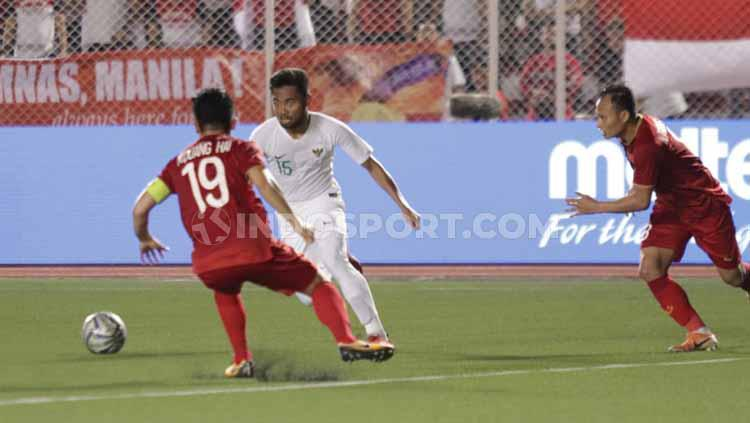 Saddil Ramdani tengah mengontrol bola dari serangan pemain Vietnam Copyright: Ronald Seger Prabowo/INDOSPORT
