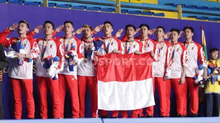 Prosesi pengibaran bendera diiringi lagu kebangsaan Indonesia Raya usai final nomor beregu putra SEA Games Filipina 2019, Rabu (04/12/19). - INDOSPORT
