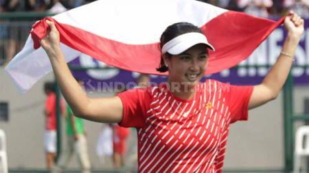 Aldila Sutjiadi mengibarkan bendera Indonesia usai meraih medali emas tenis SEA Games 2019 dari nomor tunggal putri. - INDOSPORT