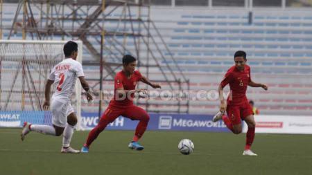 Dua pemain Timnas Indonesia U-23, Firza Andika dan Evan Dimas bekerja sama menghadapi hadangan Myanmar dalam laga semifinal SEA Games 2019. - INDOSPORT