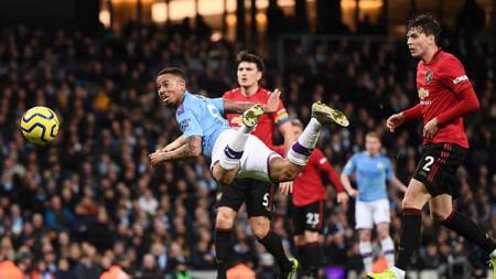 Striker Manchester City, Gabriel Jesus berusaha terbang sambil menyundul bola untuk mencetak gol ke gawang Manchester United dalam pertandingan Liga Inggris 2019-2020 bertajuk Derby Manchester - INDOSPORT