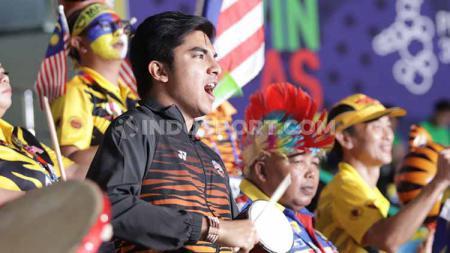 Wajah tengil Menpora Malaysia, Syed Saddiq merayakan kemenangan pasangan Aaron Chia/Soh Wooi Yik yang mengalahkan ganda putra Indonesia, Wahyu Nayaka/Ade Yusuf Santoso dalam semifinal SEA Games di Muntinlupa Sport Complex, Manila, Minggu (08/12/19). - INDOSPORT