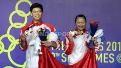 Indosport - Pasangan ganda campuran Indonesia, Praveen Jordan/Melati Daeva Oktavianti saat menerima medali emas di Final SEA Games 2019, Senin (09/12/19).
