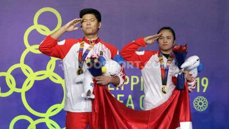 Pasangan ganda campuran Indonesia, Praveen Jordan/Melati Daeva Oktavianti saat menerima medali emas di Final SEA Games 2019, Senin (09/12/19).