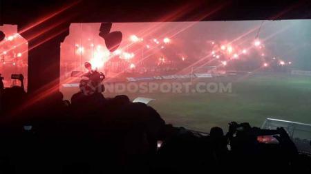 Suporter Persela meluapkan kebahagiaan batal degradasi dari Liga 1 2019 ke Liga 2 2020 dengan menyalakan puluhan flare dan kembang api di bawah derasnya hujan, pasca menang 2-0 atas Semen Padang di Stadion Surajaya Lamongan. - INDOSPORT