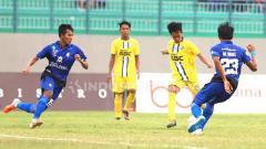 Indosport - Pemain Putra Sinar Giri, Muhammad fatikul amin (Jersey kuning) melepaskan bola dan dihadang pemain Semeru FC Lumajang Airlangga Mutamma siqdina, di Stadion Gelora Joko Samudra.
