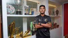 Indosport - Muhammad Rafli Mursalim berfoto di lemari trofi Persija Jakarta.