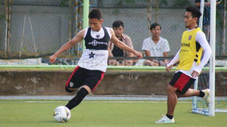 Dias Angga Putra (kiri) dibayangi M Taufik dalam sesi latihan Bali United di lapangan sintetis milik Australian Independent School (AIS), Denpasar, Bali, Selasa (7/1/20). - INDOSPORT