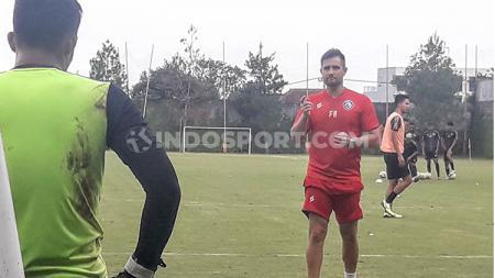 Kiper Arema FC, Teguh Amiruddin, mendengarkan instruksi dari Felipe Martins Americo. - INDOSPORT