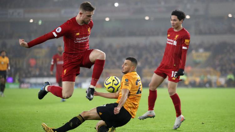 Kapten Liverpool, Jordan Henderson mencoba melewati tekel pemain Wolves Copyright: Marc Atkins/Getty Images