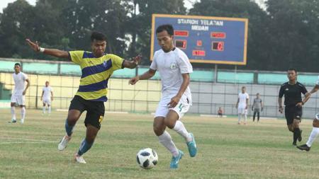 Pemain bertahan PSMS Medan, Syaiful Ramadhan (baju putih bawa bola), saat tampil di turnamen pramusim internasional Edy Rahmayadi Cup 2020, beberapa waktu lalu. - INDOSPORT