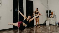 Indosport - Gisella Anastasia saat belajar pole dance ditemani oleh instrukturnya.