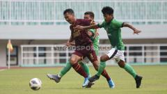 Indosport - Zulkifli Syukur (tengah) dijegal dua pemain Lalenok United.