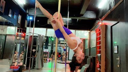 Pedangdut bertubuh seksi, Dewi Perssik membuat netizen gagal fokus usai mengalami kesulitan saat melakoni pole dance. - INDOSPORT