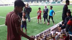 Indosport - Pratama Arhan mengambil asupan yang disediakan tim dokter untuk para pemain PSIS di Stadion Citarum.