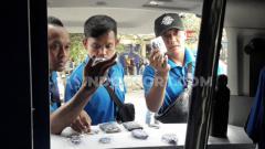 Indosport - Para penggawa Sabah FA mengisi waktu luang untuk berjalan-jalan di sekitar Stadion Kanjuruhan, sembari mencari merchandise tim Singo Edan sebagai oleh-oleh.