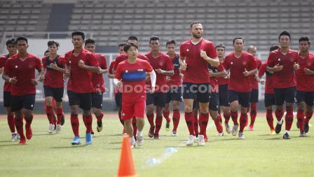 Para pemain Timnas Indonesia kompak berlari-lari kecil di lapangan Stadion Madya.