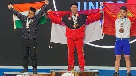 Lifter Indonesia, Muhammad Faathir (tengah) memberi kejutan setelah kembali memecahkan rekor dunia remaja cabang angkat besi pada Kejuaraan Remaja dan Junior Asia 2020 - INDOSPORT