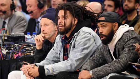 Komedian AS, Jon Stewart (kiri) dan rapper AS, Jermain Cole (tengah) serius menikmati pertandingan Kontes NBA All Star 2020.