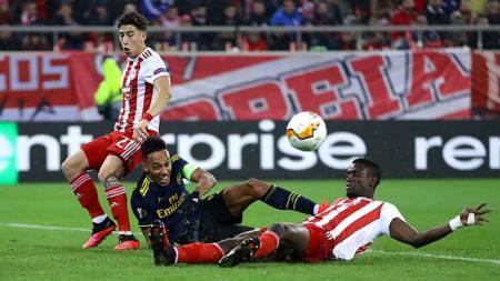 Striker Arsenal, Pierre-Emerick Aubameyang (tengah) mendapat penjagaan ketat dari dua pemain Olympiacos dalam pertandingan babak 32 besar Liga Europa 2019-2020 leg pertama. - INDOSPORT