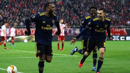 Selebrasi para pemain Arsenal saat striker mereka, Alexandre Lacazette (kiri) mencetak gol kemenangan melawan Olympiacos dalam pertandingan babak 32 besar Liga Europa 2019-2020. - INDOSPORT