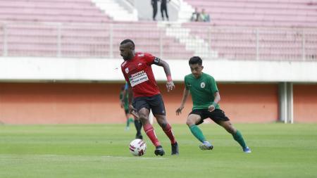 Kapten Persipura Jayapura, Boaz Solossa, dikawal pemain PSS Sleman dalam laga uji coba menjelang Liga 1 2020. - INDOSPORT