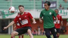 Indosport - Gelandang Persipura asal Brasil, Thiago Amaral saat berduel dengan Pemain PSS Sleman