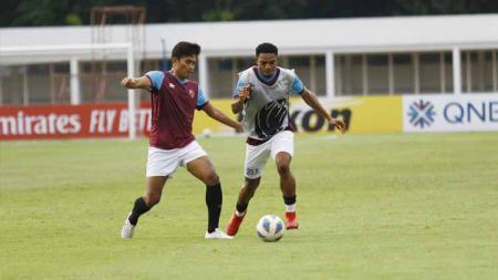 Dua pemain PSM Makassar, Ahmad Agung dan Osas Saha, saling berebut bola saat latihan di Stadion Madya Senayan, Jakarta, Selasa (25/02/20). - INDOSPORT
