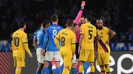 Aksi protes para pemain Barcelona saat rekannya, Arturo Vidal mendapat kartu pertama dalam pertandingan melawan tuan rumah Napoli babak 16 besar Liga Champions 2019-2020 leg pertama di San Paolo. - INDOSPORT