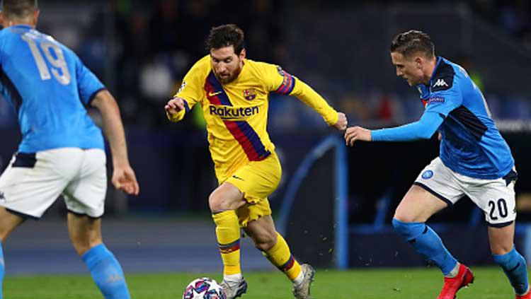 Pemain megabintang dan kapten Barcelona, Lionel Messi mendapat penjagaan dari dua pemain Napoli, Piotr Zielinski dan Nikola Maksimovic dalam pertandingan babak 16 besar Liga Champions 2019-2020 leg pertama di San Paolo. Copyright: Michael Steele/GettyImages