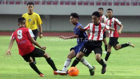 Aksi pemain Kalimantan Barat (Biru) dihadang dua pemain Sumatera Barat pada babak final Piala Soeratin U-15 2019-2020 di Stadion Manahan Solo, Sabtu (29/02/20).