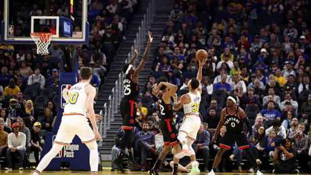 Aksi pemain megabintang Golden State Warriors, Stephen Curry saat ingin menembak bola harus dijaga oleh tiga pemain Toronto Raptors.