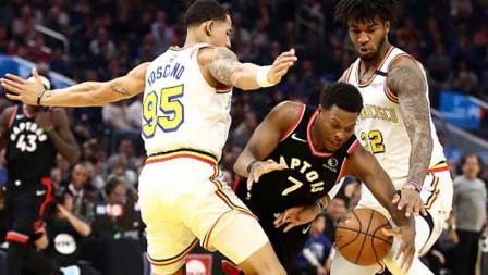 Bintang baket NBA dari tim Toronto Raptors, Kyle Lowry (tengah) dijaga ketat oleh dua pemain Golden State Warriors, Juan Toscano-Anderson (kiri) dan Marquese Chriss.
