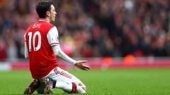 Indosport - Mesut Ozil tampak tak percaya Arsenal ditahan West Ham United di Liga Primer Inggris