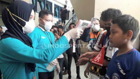 Panpel Arema FC mengecek suhu tubuh para suporter sebagai upaya mencegah virus Corona jelang laga Liga 1 kontra Persib di pintu masuk Stadion Kanjuruhan beberapa waktu lalu. - INDOSPORT