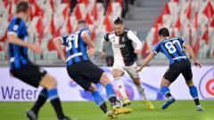 Indosport - Cristiano Ronaldo (tengah) saat berduel dengan pemain lawan pada laga Juventus vs Inter Milan di Liga Italia 2019-20, Senin (09-03-20).
