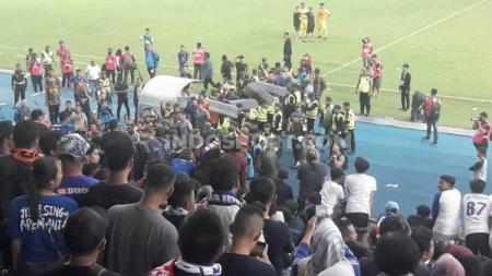 Ulah segelintir suporter yang melempari pemain masuk ke ruang ganti dalam laga Liga 1, Arema FC vs Persib Bandung. - INDOSPORT
