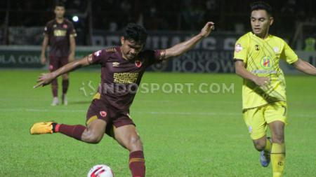 Bek kanan PSM Makassar, Asnawi Mangkualam (merah marun), mencoba melewati hadangan pemain Barito Putera, Ambrizal Umanailo (kuning). - INDOSPORT